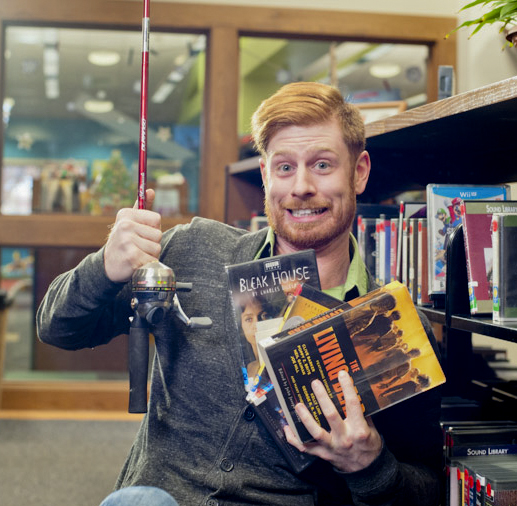 Photo of Garland County Library Patron with books, movies, cds and a fishing pole